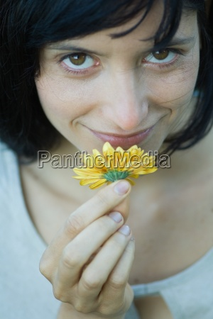 young woman smelling flower smiling at
