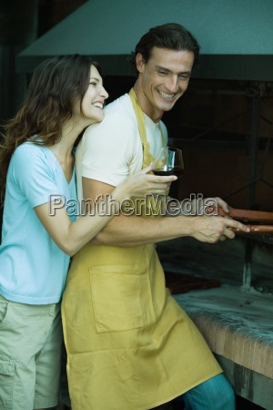 couple standing by barbecue woman holding