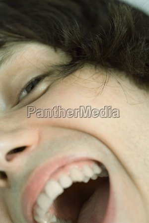 cropped view of teenage boy laughing