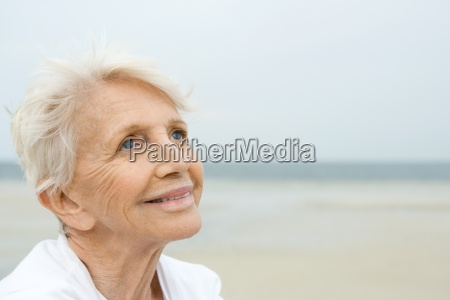 senior woman smiling looking up beach
