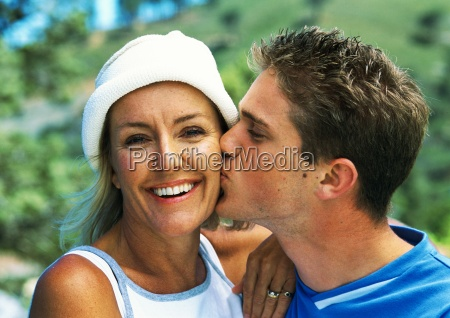 teenage boy kissing mature womans cheek