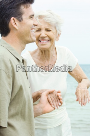 senior woman and adult son holding