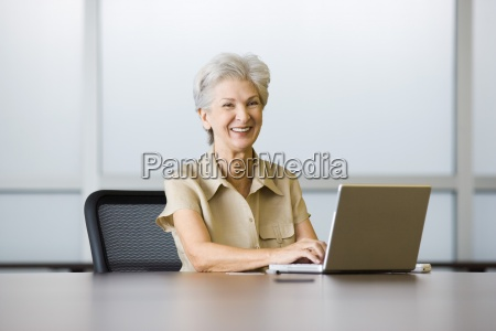 senior woman sitting at desk using