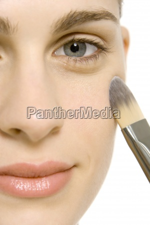 woman applying make up to cheek