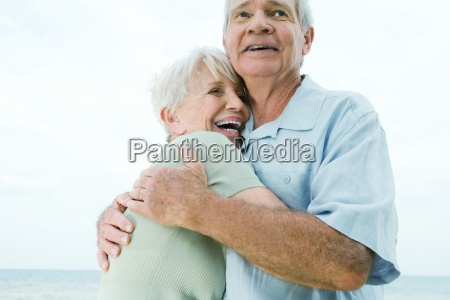 senior couple hugging woman laughing low