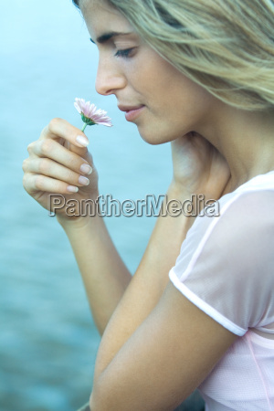 young woman smelling flower profile close