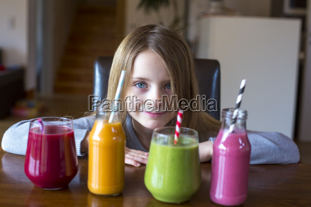 portret usmiechniete dziewczyny siedzacej przy stole