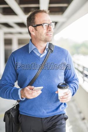 biznesmen z telefonem komorkowym i kawa