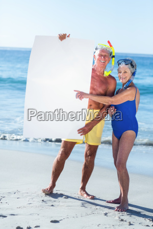 senior couple with beach equipment holding