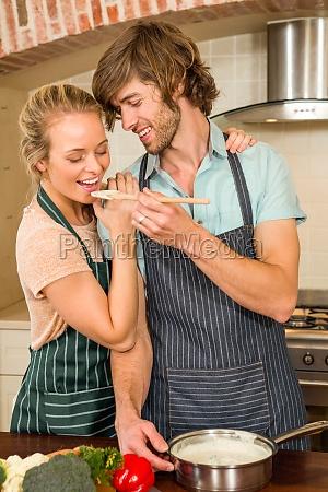 handsome man making his girlfriend taste