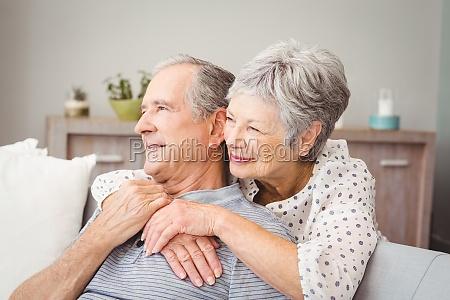 romantic senior couple sitting in living