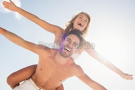 boyfriend giving piggy back to girlfriend