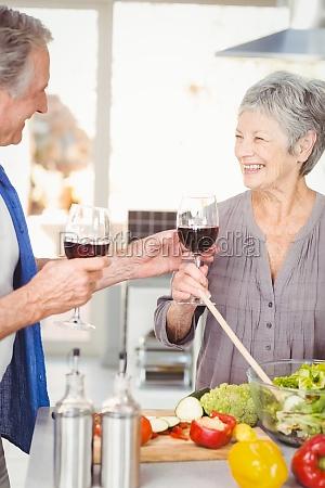 happy senior man offering red wine