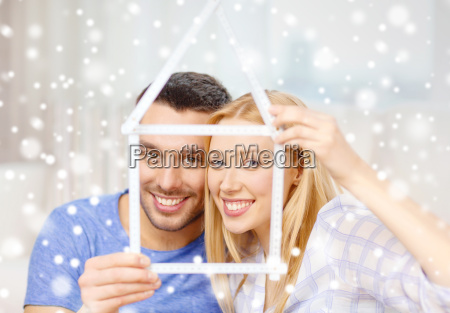 smiling couple holding house model at