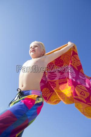 portrait of boy holding towel above