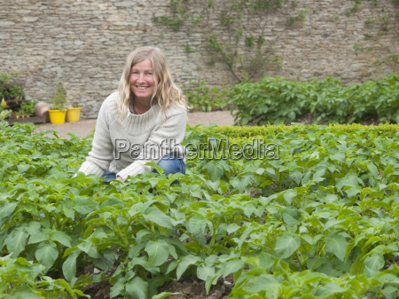 portrait of woman gardening with potato