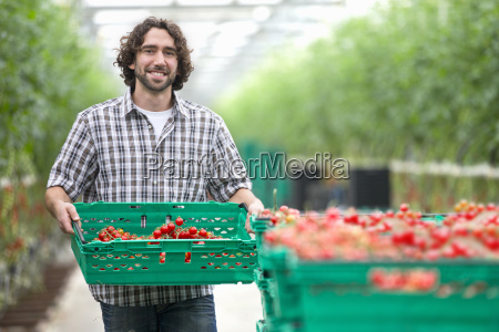 portrait of grower carrying crate of