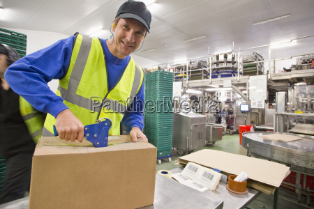 portrait smiling worker taping box in