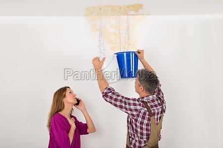 pracownik zbieranie wody w wiadrze od