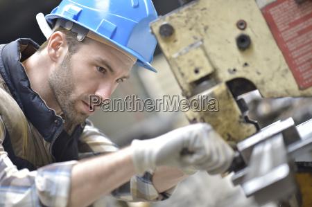 pracownik przemyslowy pracujacy na maszynie w
