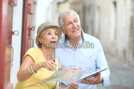 starsi turysci spaceruja po ulicy z
