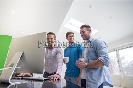 znajomi zgromadzeni wokol komputera