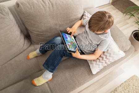 boy using digital tablet for playing
