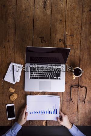 man with charts at his desk