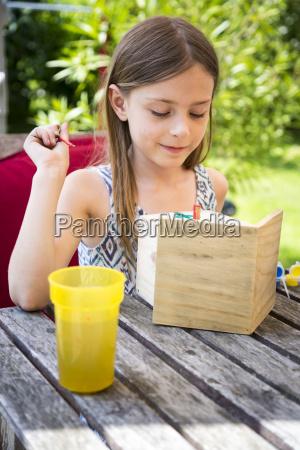 portrait of girl painting birdhouse