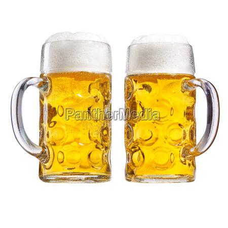 dwie szklane tankards schlodzonego piwa piankowego