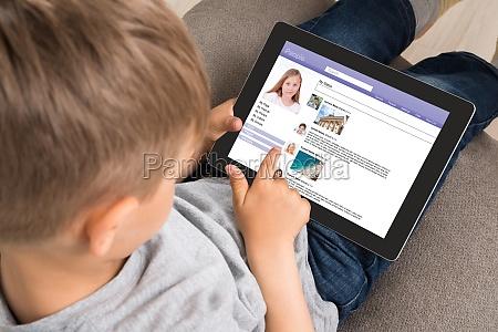 cute little boy using social networking