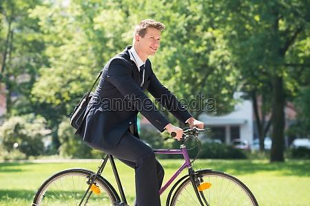 biznesmen jazda na rowerze w park