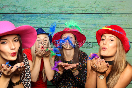 women with hats blowing colorful feathers