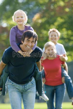 family piggy backs in the park