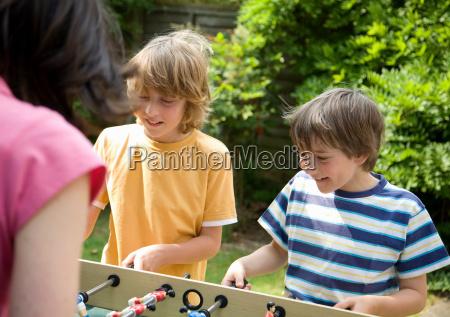 two boys playing table football