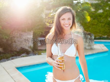 woman in bikini drinking beer by