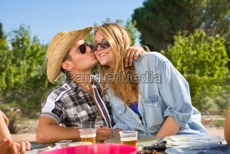 young man kisses young woman on