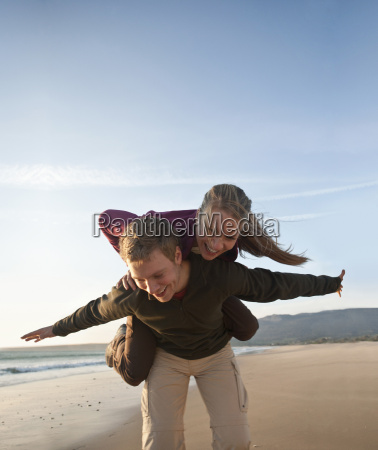 young man giving woman piggyback ride