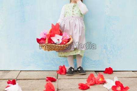 dziewczyna trzymajac kosz papierowych kwiatow