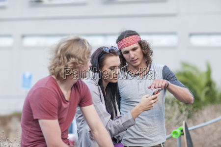 three young adult friends looking at