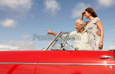 senior couple in sports car pointing