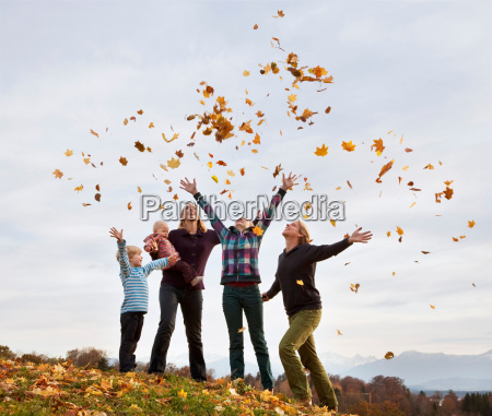 family throwing autumn leaves into air