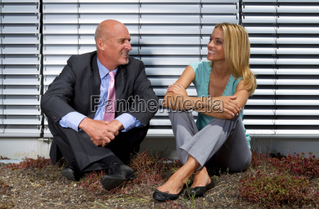 business people sitting in grass