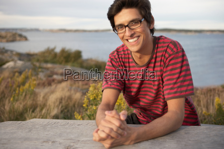 young man outdoors sitting at table