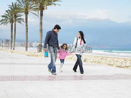mother and father walking with daughter