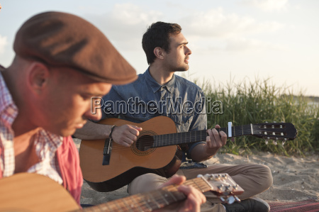 two adult male friends playing acoustic