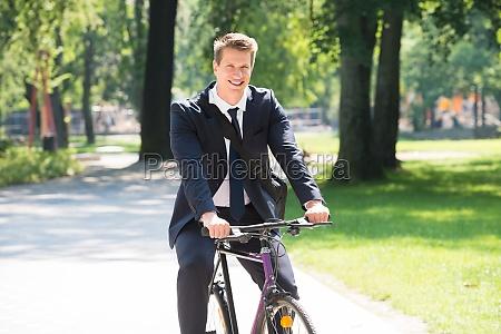 biznesmen jazda rowerem w parku