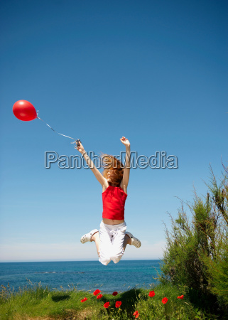 young girl jumping with red balloon