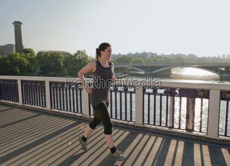 woman running over bridge