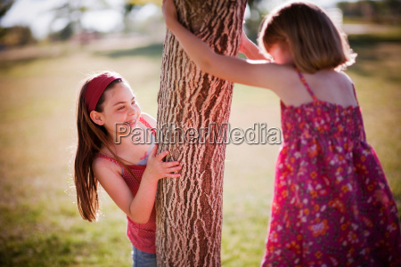 2 young girls playing around tree